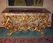 Console en bois sculpté et doré, plateau en marbre rouge. Obelisco Premium S.r.l.