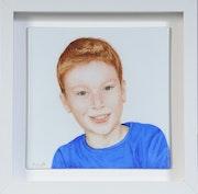 Portrait d'un jeune garçon espiègle, souriant.