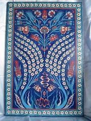 Panneau de lave de volvic à décor floral sur fond bleu.