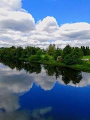 Bonito paisaje con nubes reflejadas en el rio.