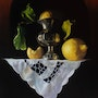 Lemons, pewter vase and lace cloth.