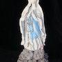 Vierge sur des rochers surplombant un village. Marie D