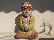 Bouddha méditeur avec petite bougie.