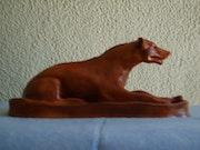 Création d'une statue en argile rouge représentant une hyène.