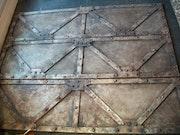 Paravent de bois peint en ferraille partiellement rouillée.