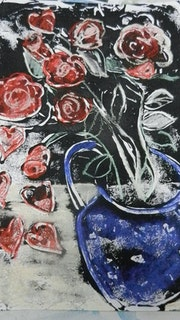 Red roses in a blue jug.