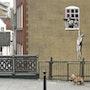 Man hanging at window. Banksy