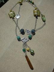 Long collier en perles vertes, jaunes et turquoises.