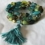 Bracelet de 3 rangs de perles ceramiques tonalites bleu vert avec pompon turquoi. Jigée