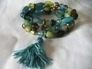Bracelet de 3 rangs de perles ceramiques tonalites bleu vert avec pompon turquoi.